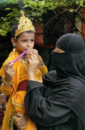 A Muslim woman carries her son, dressed as Lord Krishna, on the occassion of Janamashtami in Patna