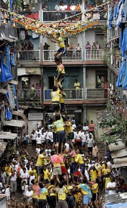 Devotees form a human pyramid to reach a vessel containing butter during Janmashtami celebrations in Mumbai