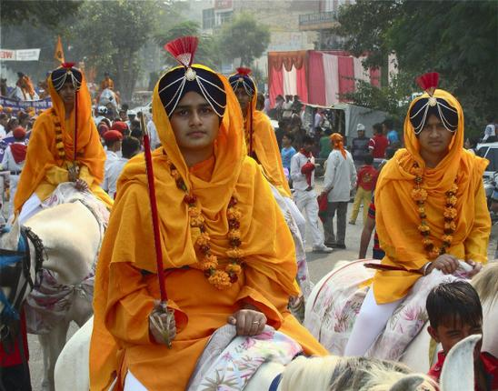 Sikh girls ride horses during a Shobha Yatra on the occasion of the birth anniversary of Guru Nanak Dev in Faridabad