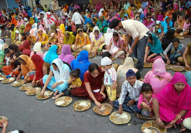 Women and children eat at a community kitchen or 'langar' at Nakka Gurudwara on the occasion of Guru Nanak Jayanti in Lucknow